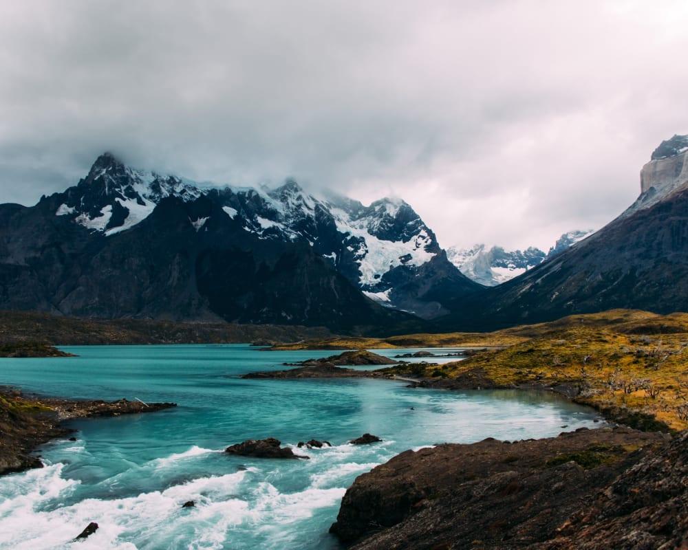 eisblauer Fluss und schwarze Berge mit Schnee in Patagonia