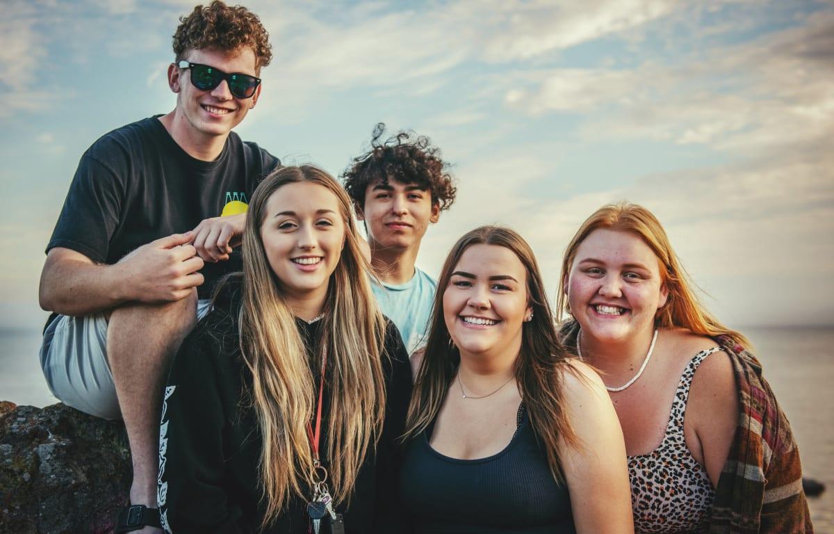 Gruppe von 3 jungen Frauen und 2 jungen Männer, die alle in die Kamera lächeln, da sie Reisepartner gesucht und für immer gefunden haben.