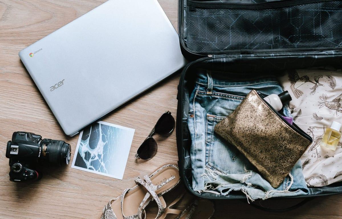 Geöffneter Koffer mit Kleidung und einer glitzernden Kosmetiktasche. Daneben liegt ein acer laptop, eine Kamera, eine schwarze Sonnenbrille und gemusterte Sandalen