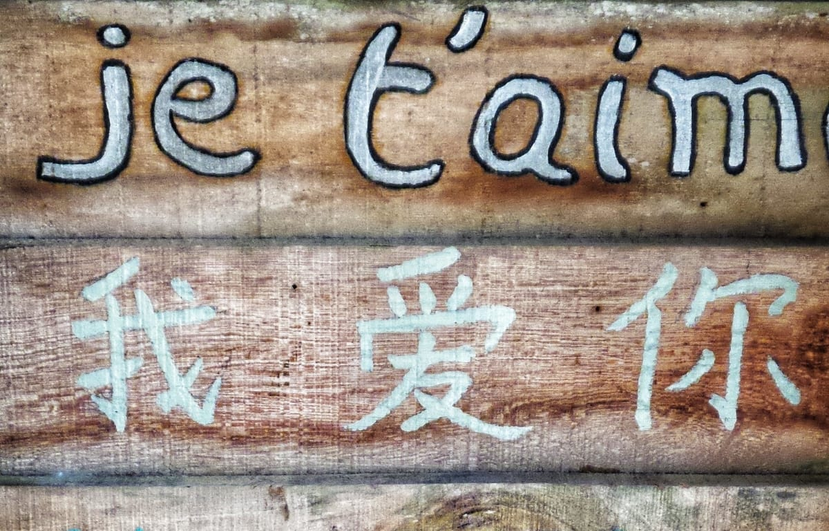 The words I love you written in two different languages on a wooden board