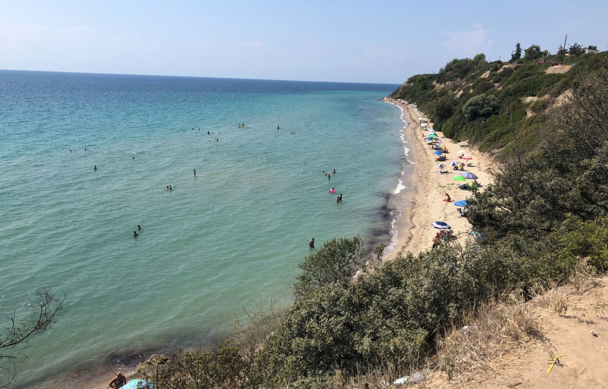 Kleine Bucht auf Chalkidiki in Griechenland mit einigen Menschen im Wasser und bunten Handtüchern auf dem Strand