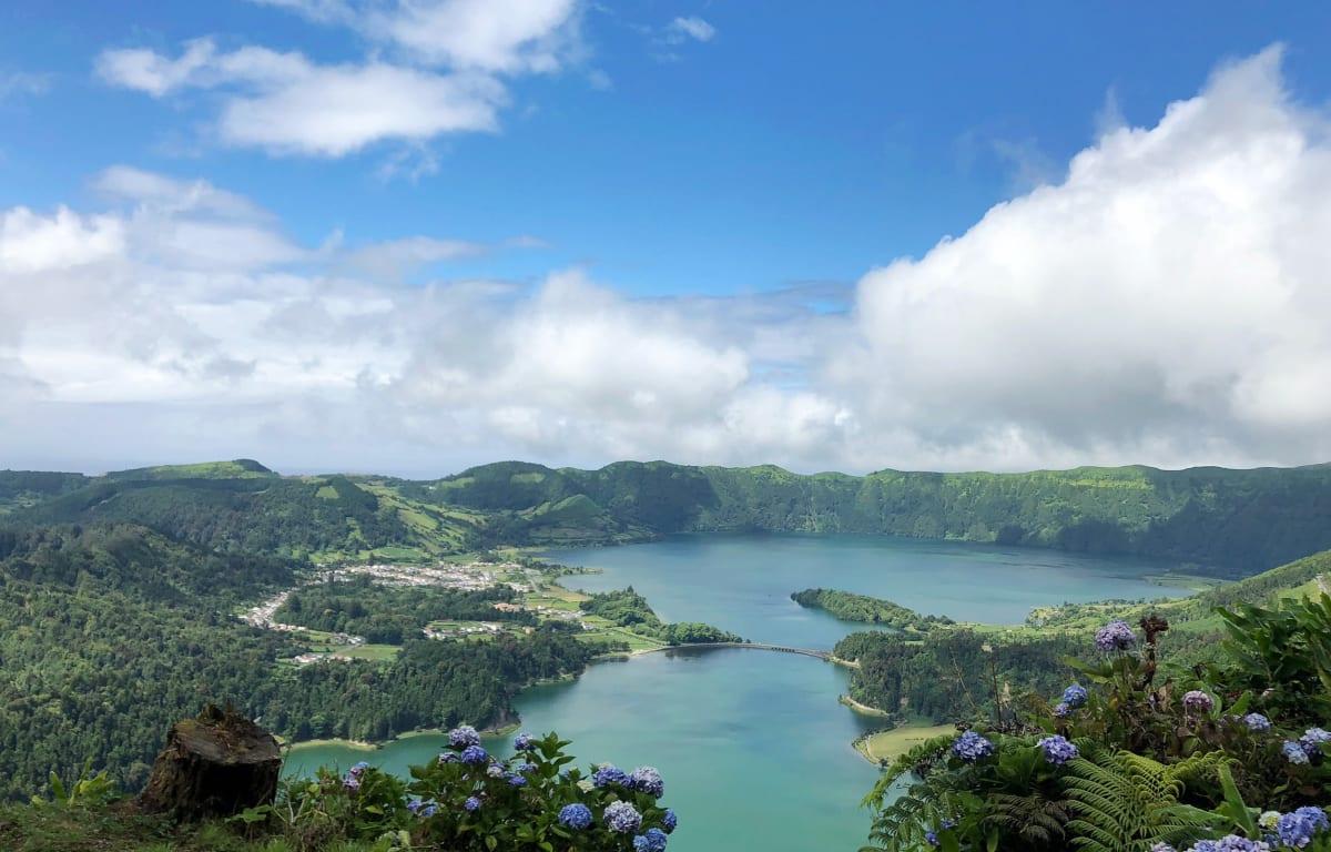 Kratersee auf den Azoren mit blauen Hortensien im Vordergrund und einem kleinen Ort am Ufer. Die Azoren sind perfekt für eine Schnorchelreise