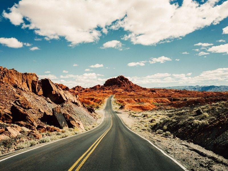 Lange verlassene Straße in einem Wüstengebiet mit Gebirge