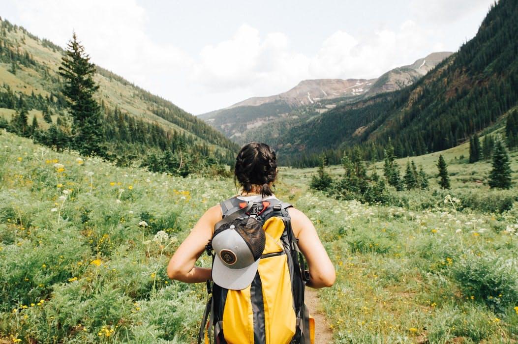 Frau mit gelbem Rucksack wandert in bergiger Umgebung, von hinten zu sehen