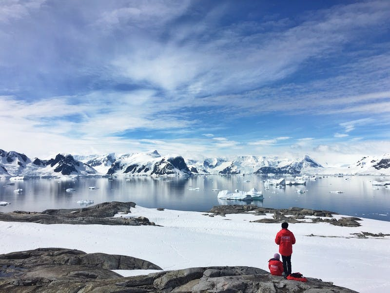 Gletscher und Eiswasser am Südpol mit zwei Personen in rot gekleidet