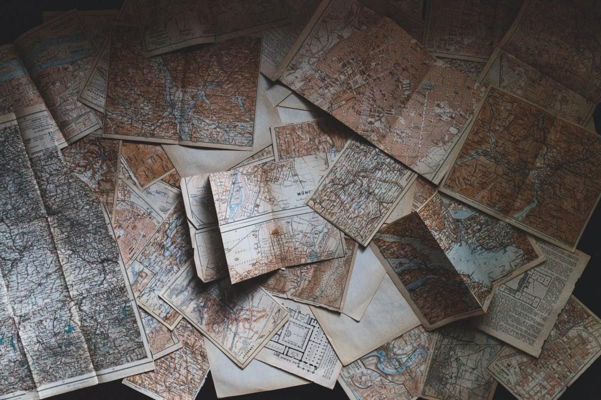 Weltkarten auf Papier ungeordnet übereinandergelegt.