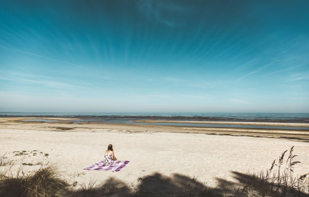 Frau sitzt auf einem rot-weiß karierten Tuch am weiten Strand mit Schilf im Vordergrund und der Ostsee im Hintergrund. Darüber erstreckt sich sehr strahlend blaue Himmel