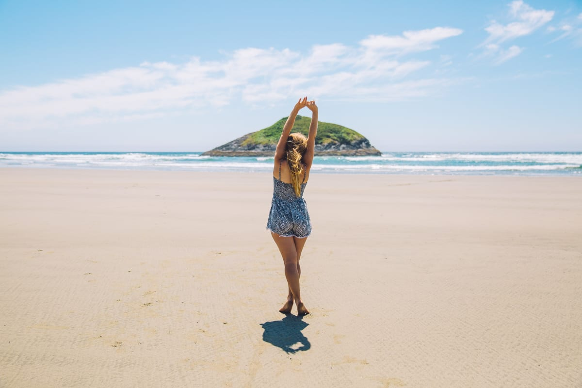 girl holding up her arms on the beach