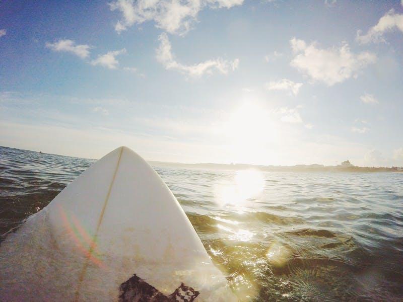 Weißes Surfbrett im Wasser unter blauem Himmel