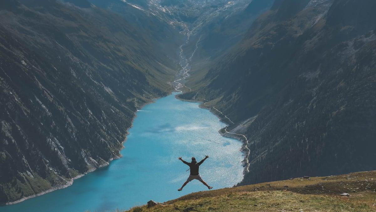Reisebegleitung springt in die Luft über einem tiefblauen Fjord.