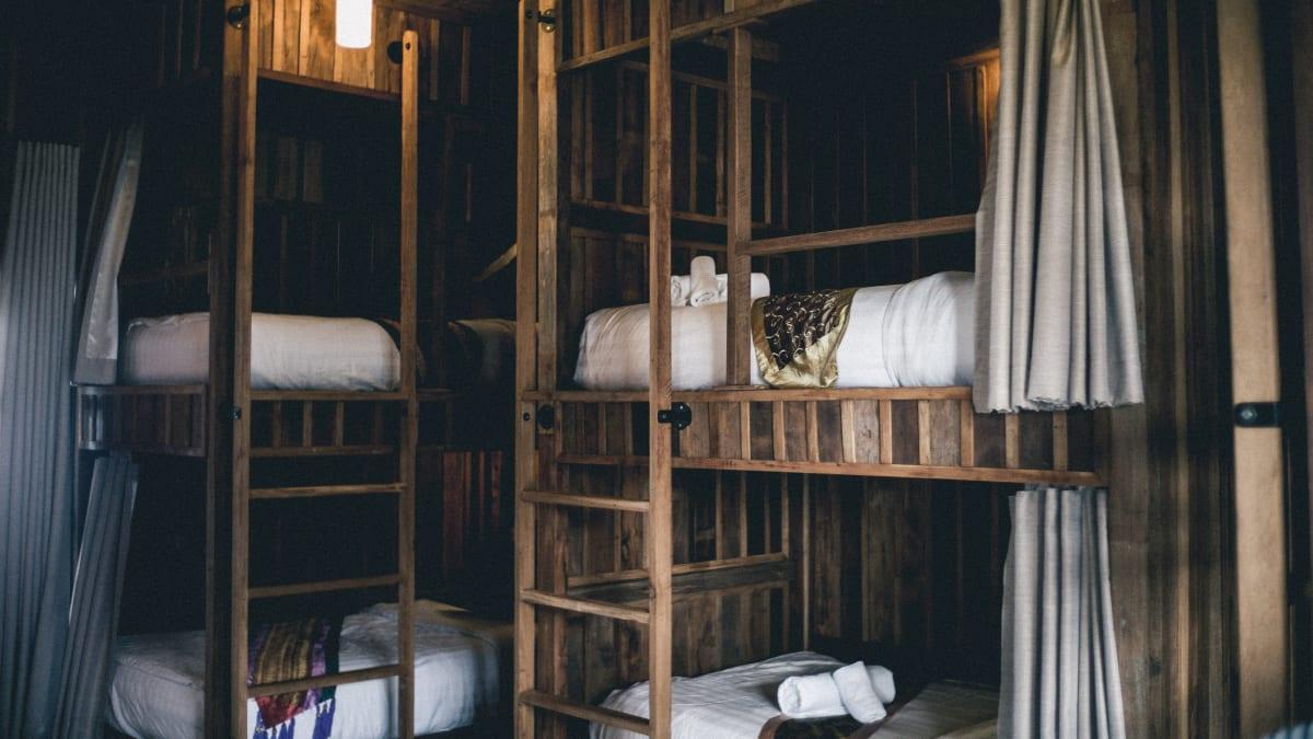 Mehrbettzimmer aus dunklem Holz und weißen Bettdecken und Kissen in einem Hostel.