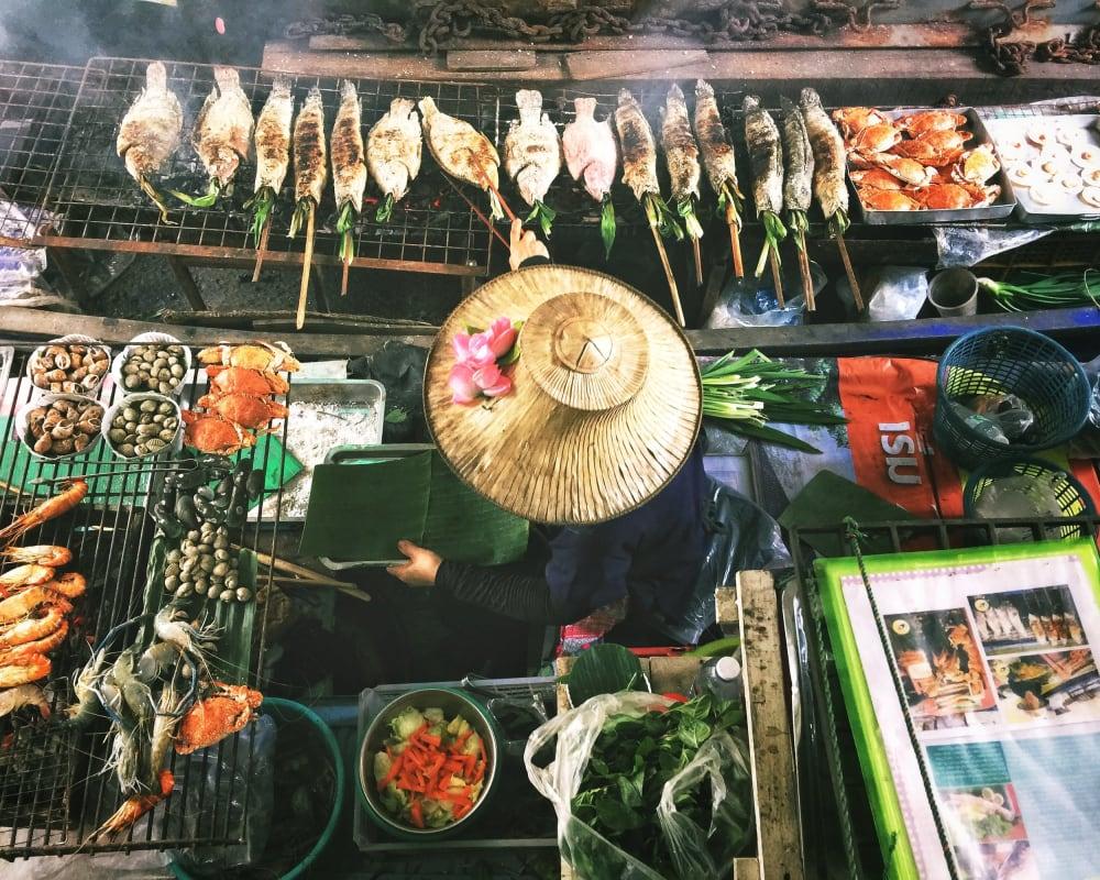 Frau mit einem Strohhut auf einem Straßenmarkt umringt von asiatischem Essen