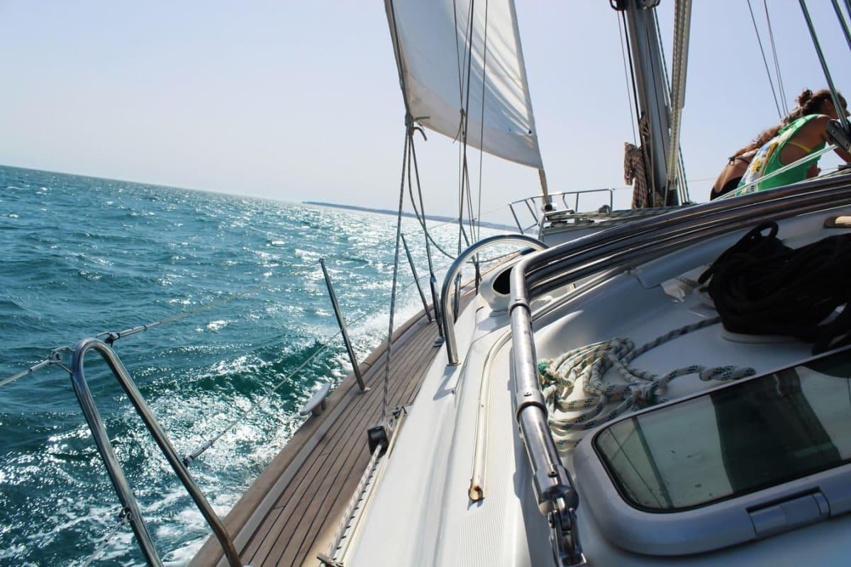 Nahaufnahme der linken Seite eines Bootes mit Boden, Reling und Teil des Segels