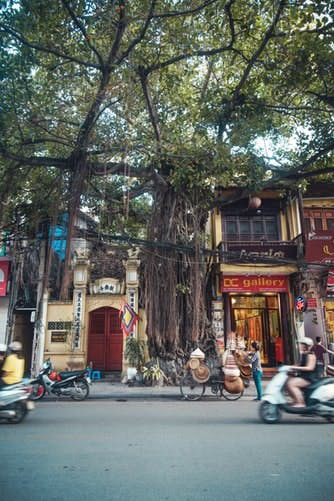 Central street in Hanoi accommodates motorcyclists, cars, cafes, shops and trees for winter travel