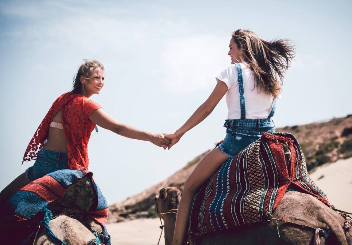 2 Frauen reiten auf Kamelen, halten sich an der Hand und gucken sich an