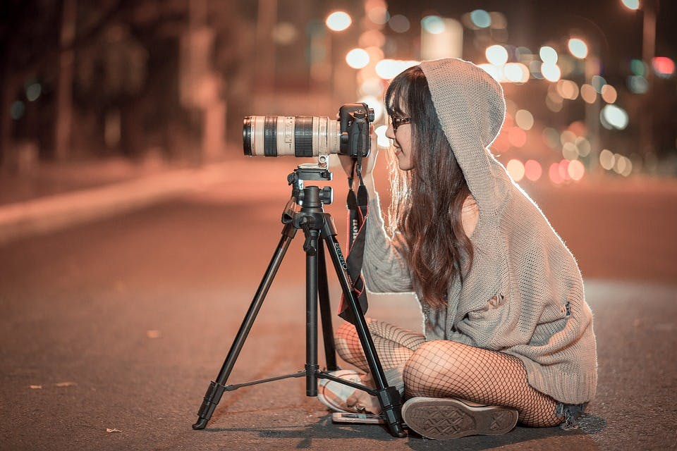 a girl sat on the floor taking pictures with a camera