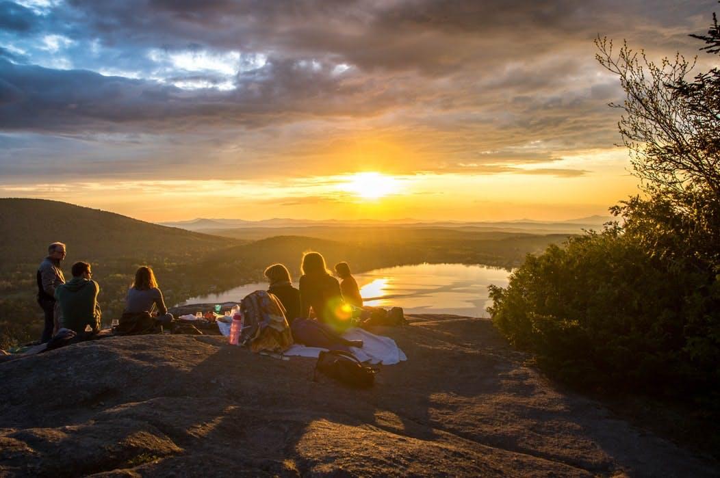 6 Menschen sitzen bei Sonnenuntergang auf einem Berg, Blick über das Tal