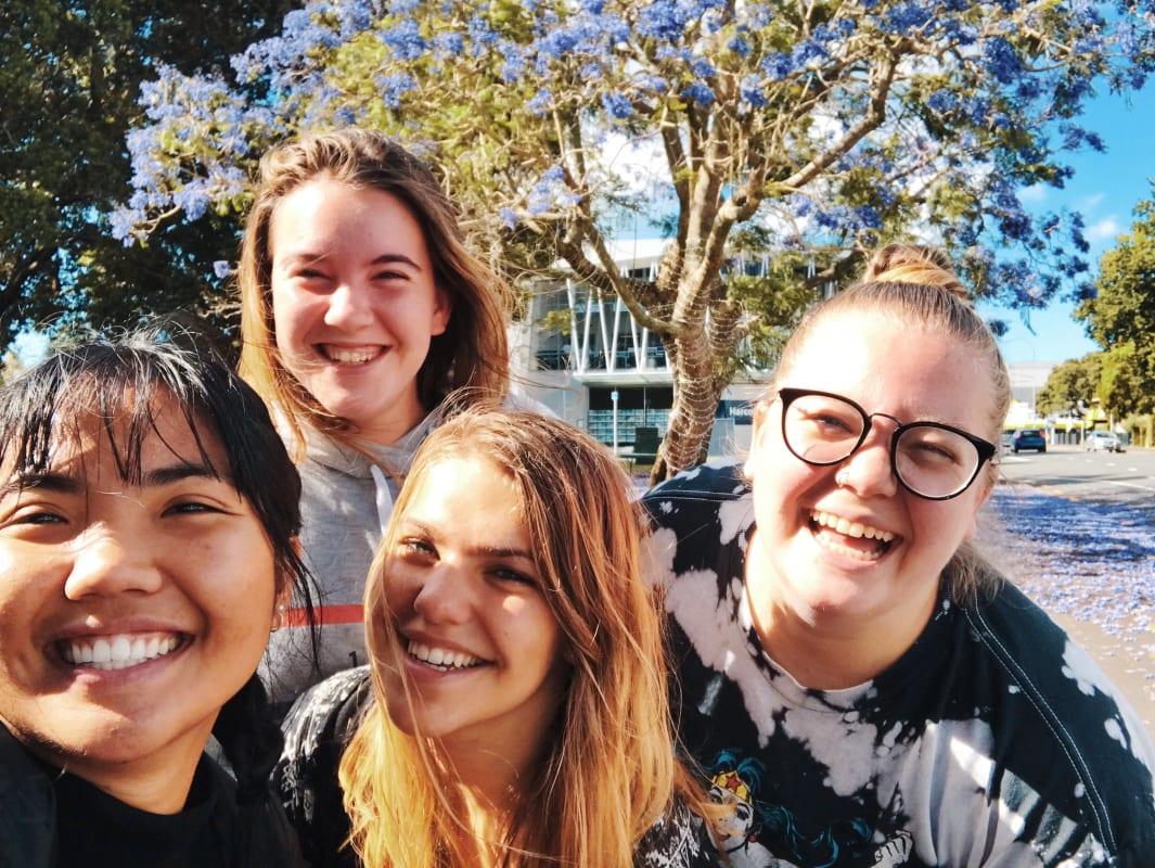 Reisegruppe von 4 jungen Frauen lacht in die Kamera in der Sonne