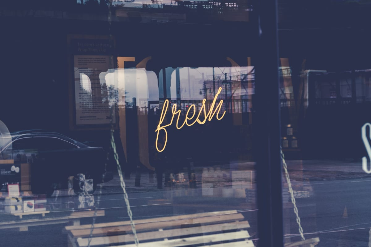 a neon sign reading fresh
