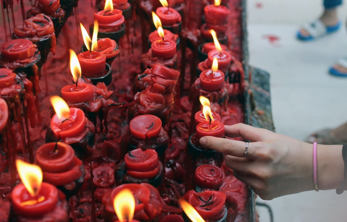 rows of red candles that have been already lit by a woman's hand