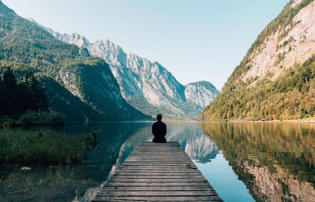 Mann sitzt auf einem hölzernen Steg am Königssee in Bayern, umgeben von hohen Bergen. Ein sehr inspirierender Ort.