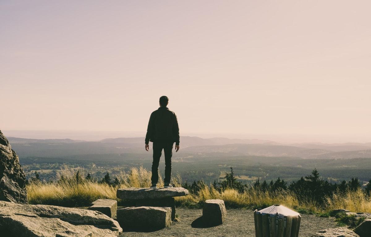 Mann steht auf einem Berg im Mittelgebirge Harz und schaut in die tiefen Täler hinunter.