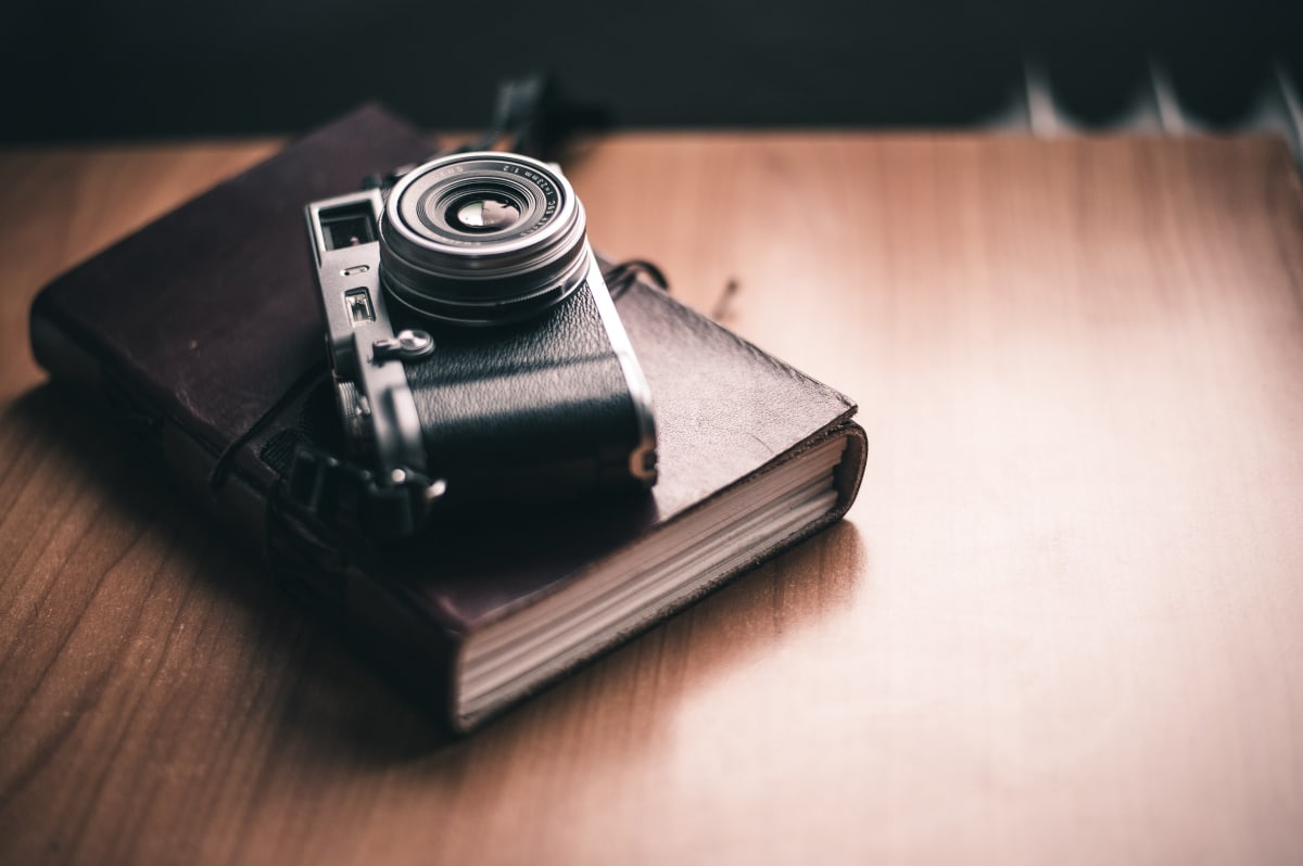 a camera lying on top of a photo album