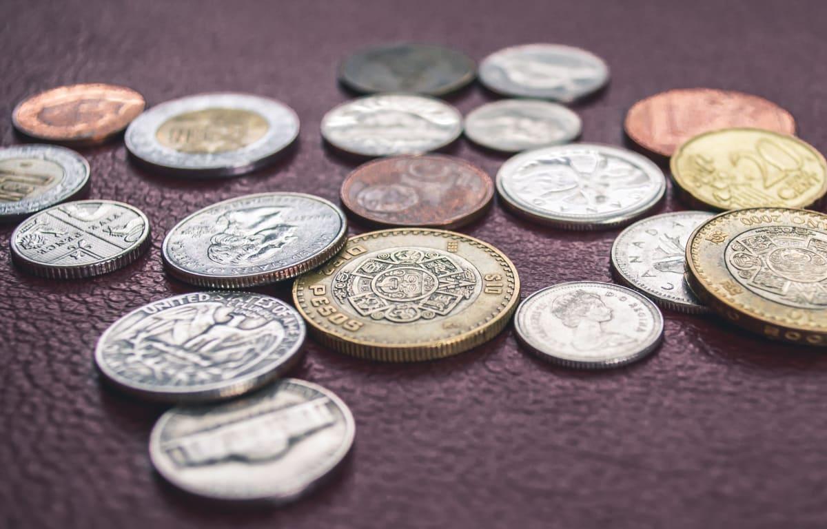 Zahlreiche Geldmünzen aus verschiedenen Ländern, darunter Pesos, Dollar Cents und Euro Cents