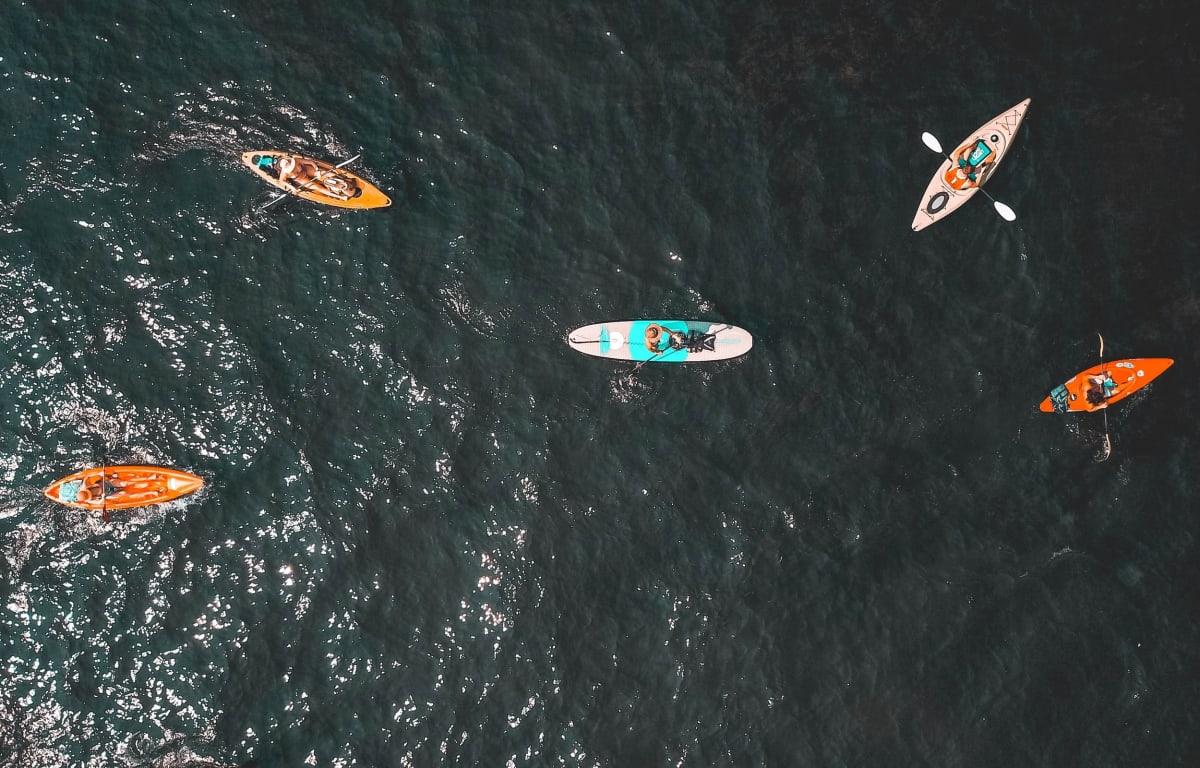 Eine Gruppe Reisepartner fährt mit Kanus auf einem See bei einem Campingplatz