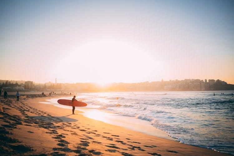 Surfer in Australien am Strand vor einem Sonnenuntergang