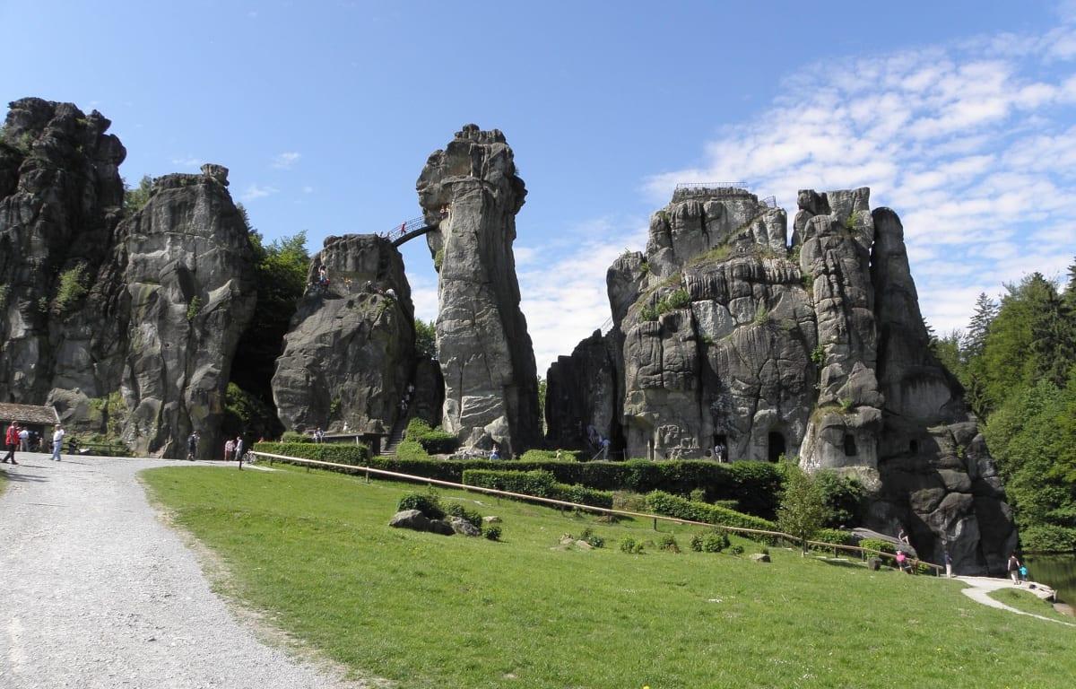 Die Externsteine in Nordrhein-Westfalen unter blauem Himmel und einer Treppe zwischen den Felsformationen