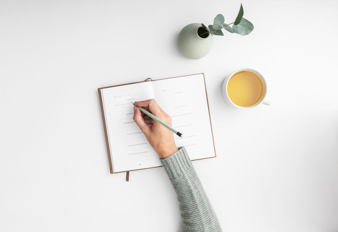 a diary being written with a cup of tea next to it