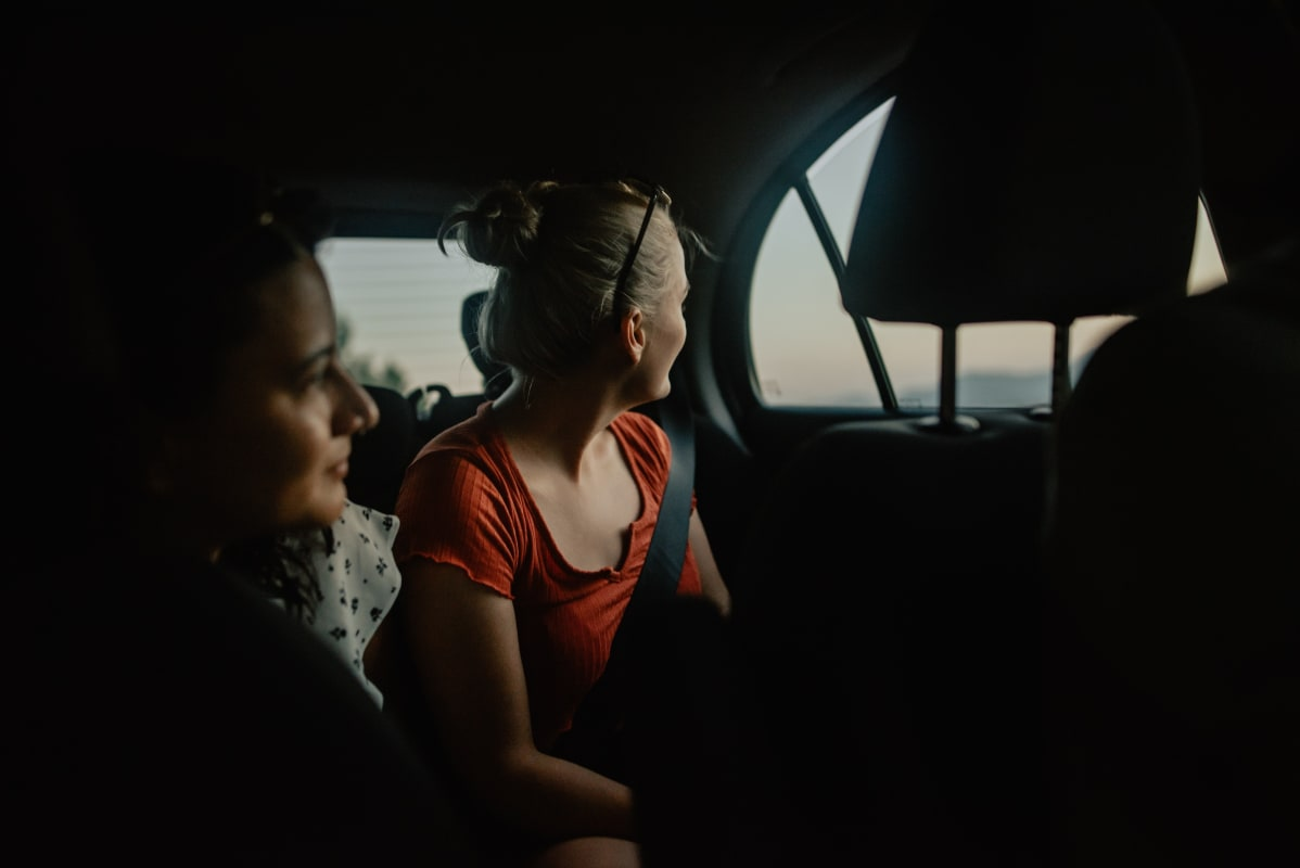 two girls sat in a car looking out of the window