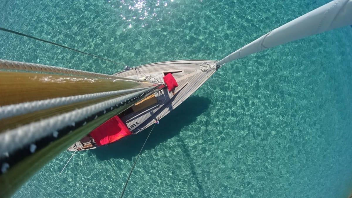 Blick von Mast runter auf Segelboot in klarem Wasser