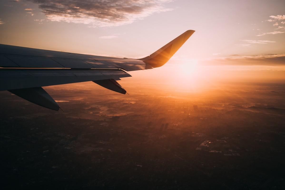 Bild eines Flugzeugflügels fotografiert aus dem Flugzeug im Sonnenuntergang