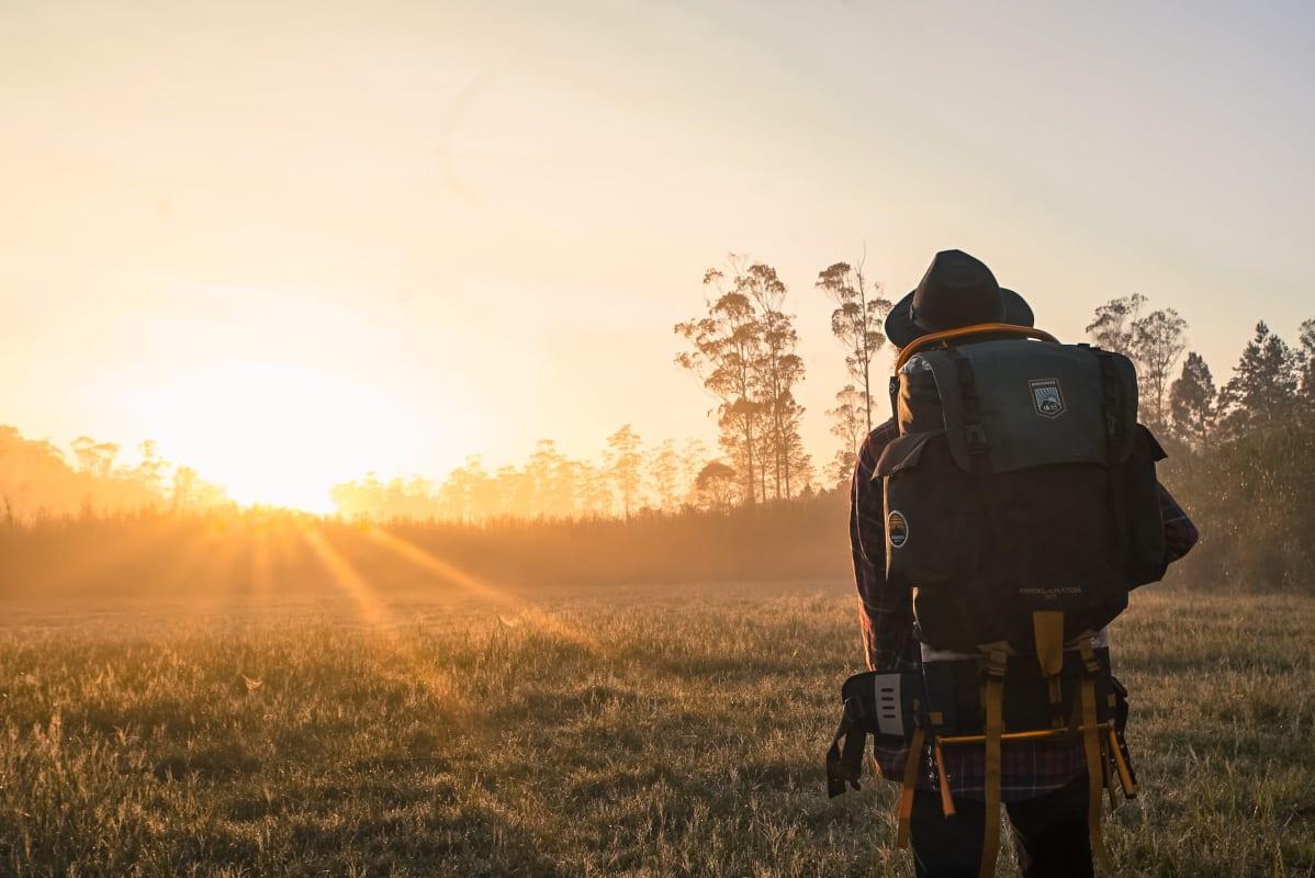 ein mann mit rucksack der den sonnenunterang anschaut