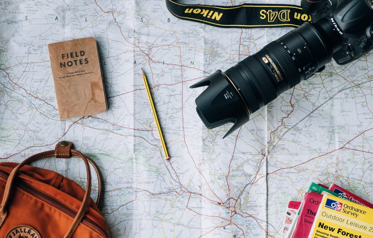 Orange backpack, a small brown notebook, travel magazines and a Nikon D4s camera lying on a street map