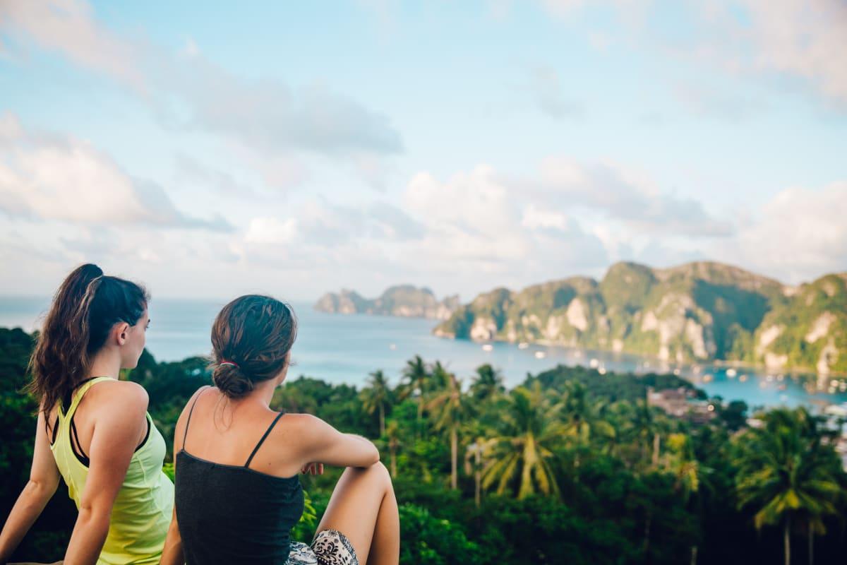 Zwei junge Frauen sitzen auf einem Hügel mit Blick auf eine Bucht und einen dichten Urwald