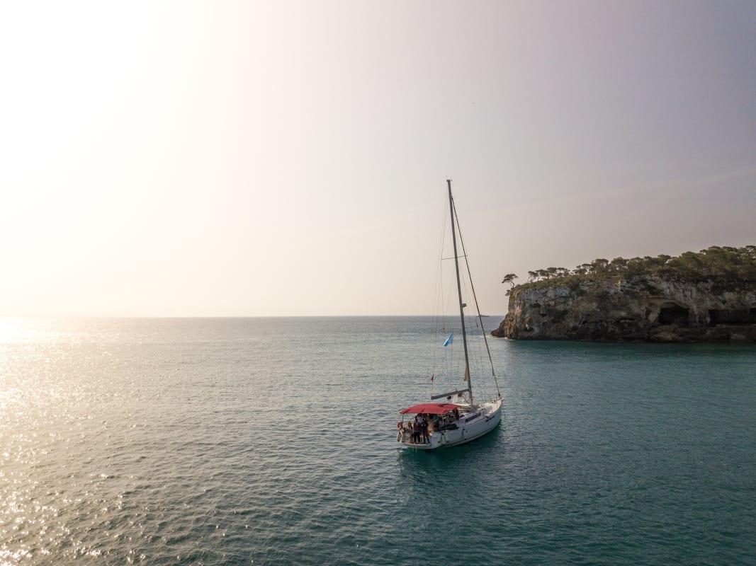 Segelboot in Gewässer bei Sonnenschein, im Hintergrund ein Stück Land