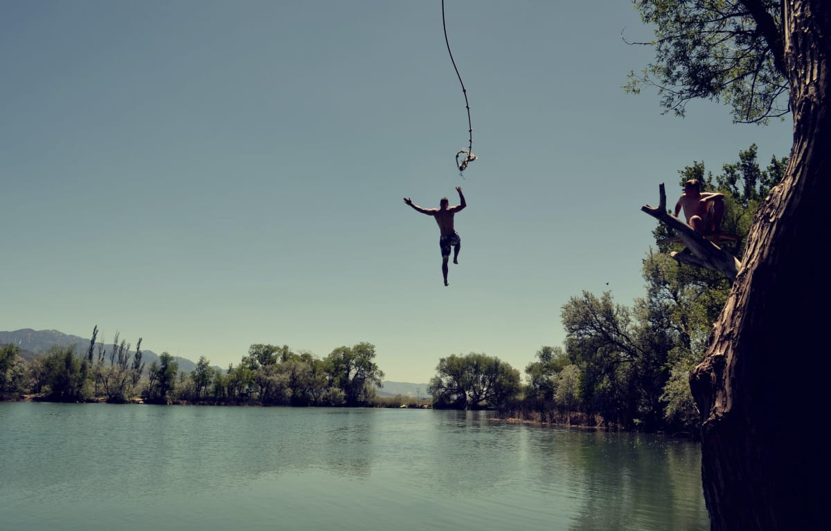 Man jumps on a rope into a blue lake, Travel Buddy is waiting on a branch.