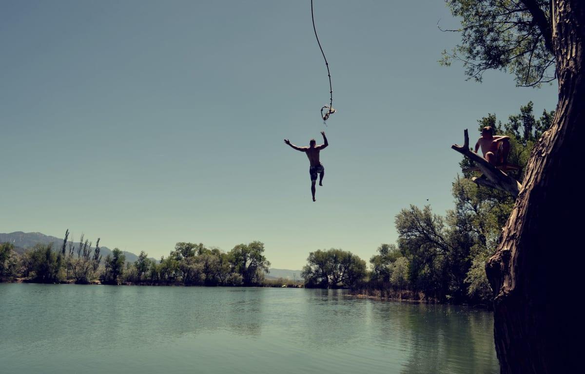 Mann springt an einem Seil in einen blauen See, Reisepartner wartet auf einem Ast.
