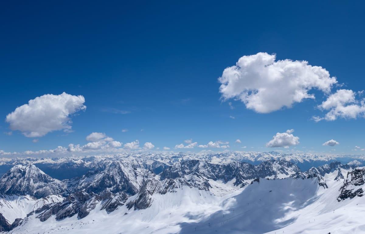 Die Zugspitze in Bayern mit Schnee bedeckt und blauem Himmel. Dort gibt es Camping in Iglus.