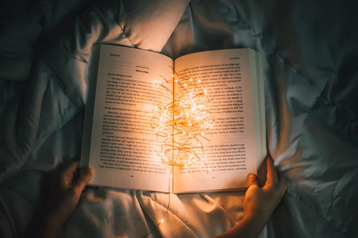 a book being read in bed with fairy lights