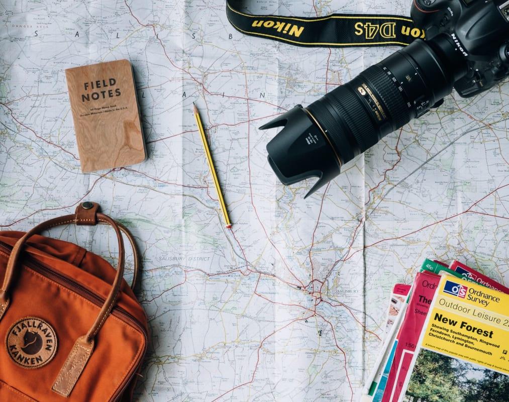 Stadtführer, Stifte, Notizen, Reisepläne und Kamera auf einer Landkarte
