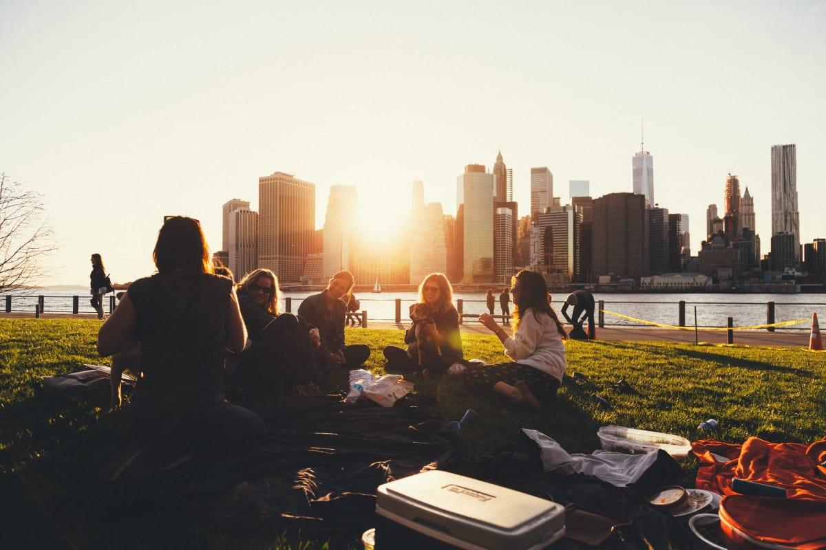 Reisepartner mit Picknickkorb auf einer Wolldecke im Gras vor der Skyline von New York in den USA im Sonnenuntergang