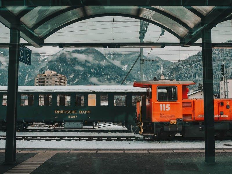 Alter Eisenbahnwaggon mit rotem Fahrerhaus vor einem Gebirge