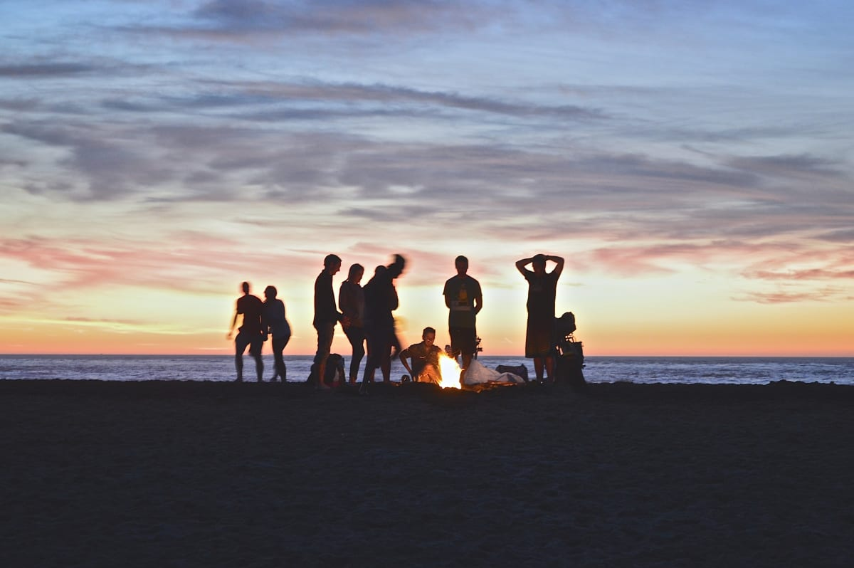 group of people standing over a bonfire