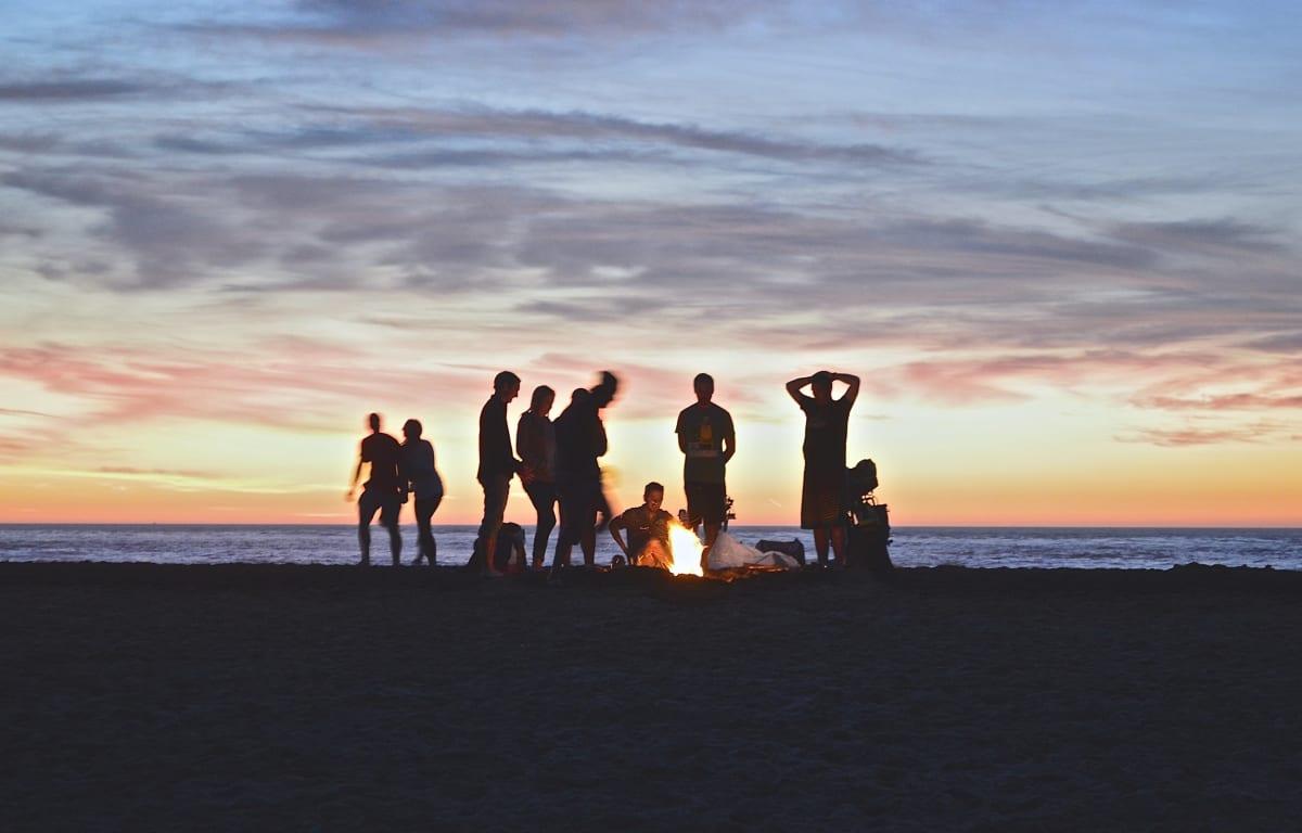 Gruppe von Personen in einer Gruppenreise an einem Lagerfeuer im Sonnenuntergang