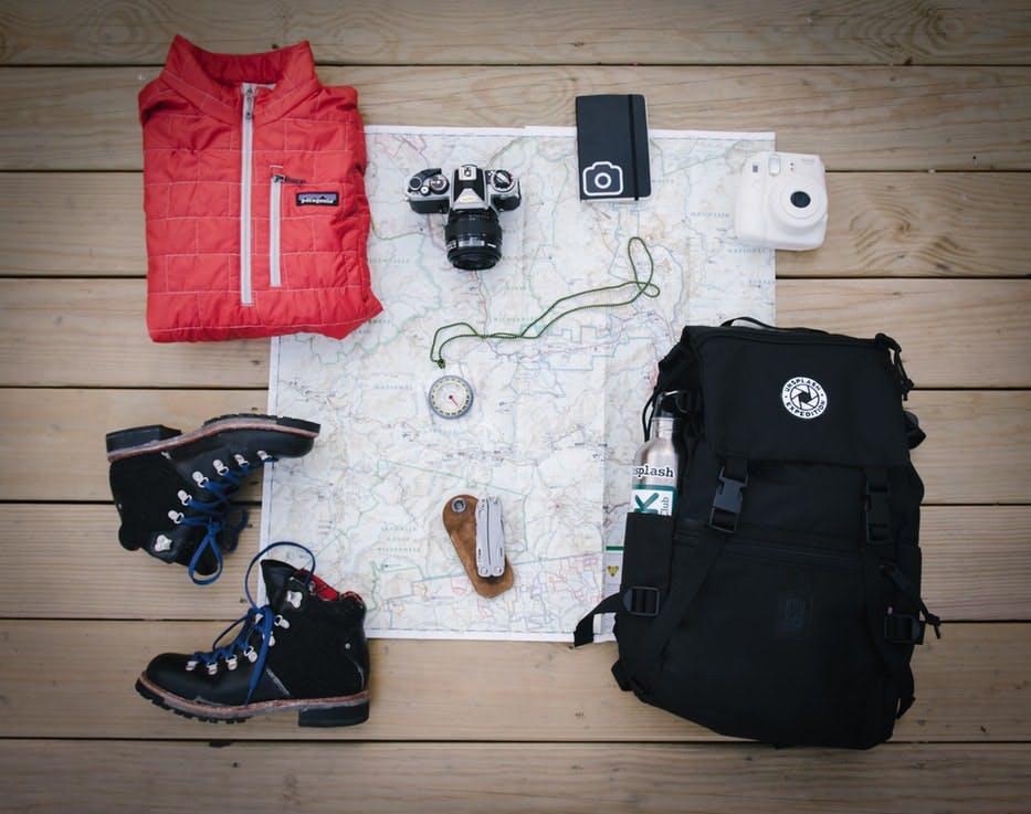 Schwarzer Rucksack, Jacke, Schuhe und Kleinigkeiten ausgebreitet auf Landkarte