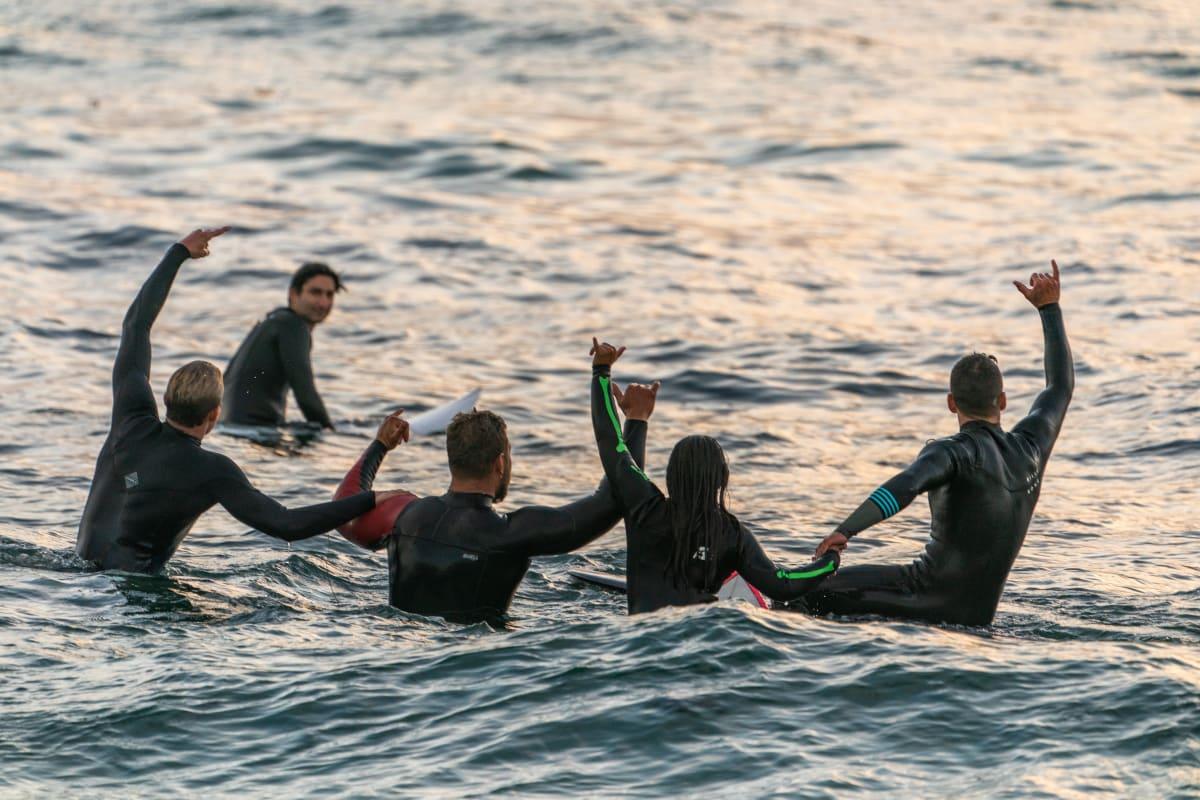 Eine Gruppe von 5 Surfern auf dem Wasser in schwarzen Neoprenanzügen. Alle zeigen das Surferzeichen in die Luft.